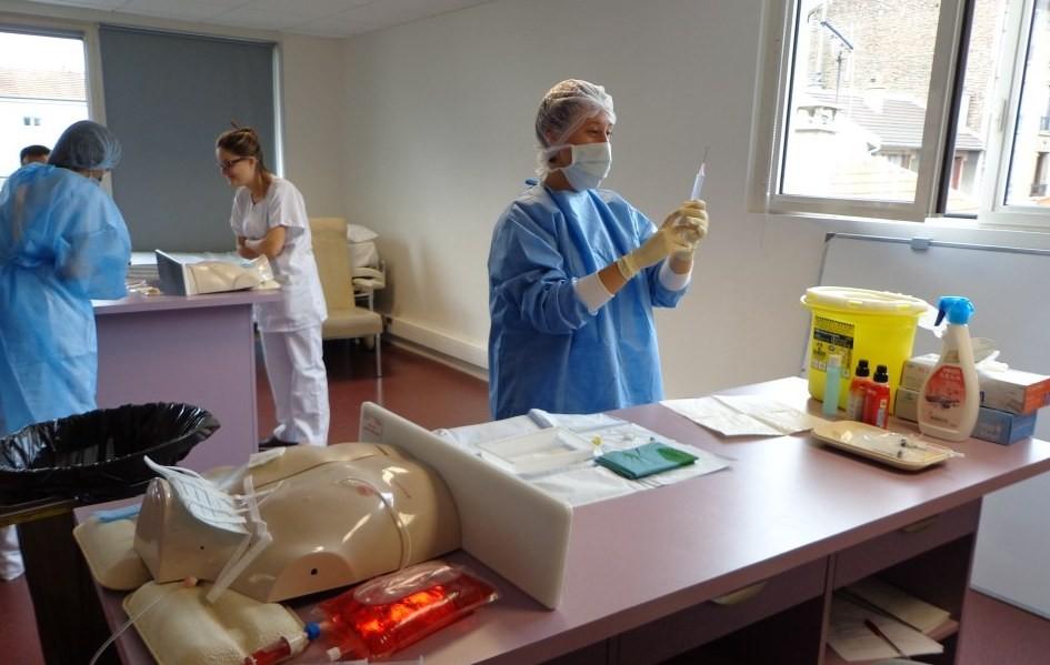 Etudiants infirmiers en train de s'entraîner aux soins dans une salle de travaux pratiques polyvalente