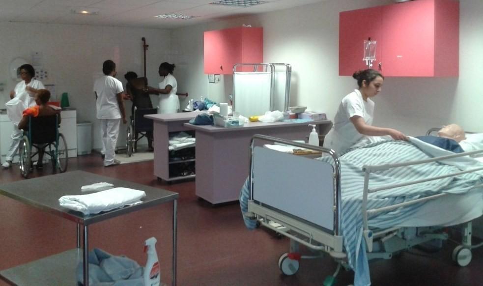 Etudiants aides-soignants en train de s'exercer dans une des salles de travaux pratiques